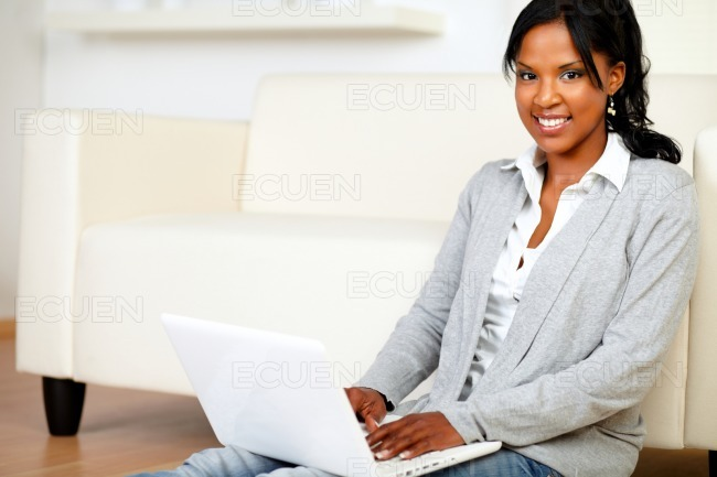 Relaxed young woman smiling at you with a laptop stock photo