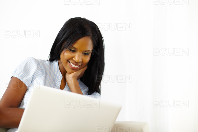 Relaxed young woman working on laptop stock photo