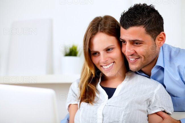 Romantic young couple at home looking to laptop stock photo