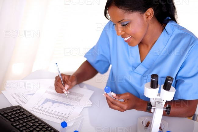 Scientific woman working with test tube and notes stock photo