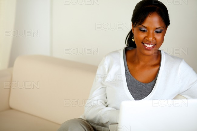 Smiling afro-American woman using laptop stock photo