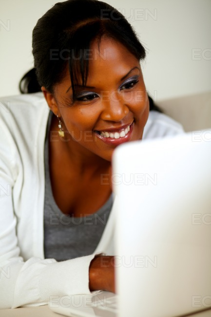 Smiling black female looking on laptop screen stock photo