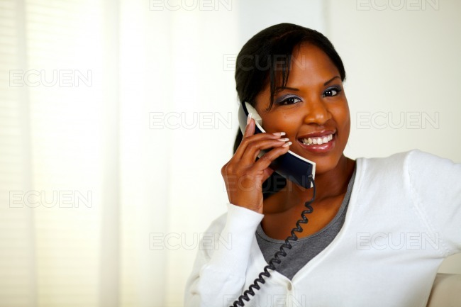 Smiling black woman looking at you while talking stock photo
