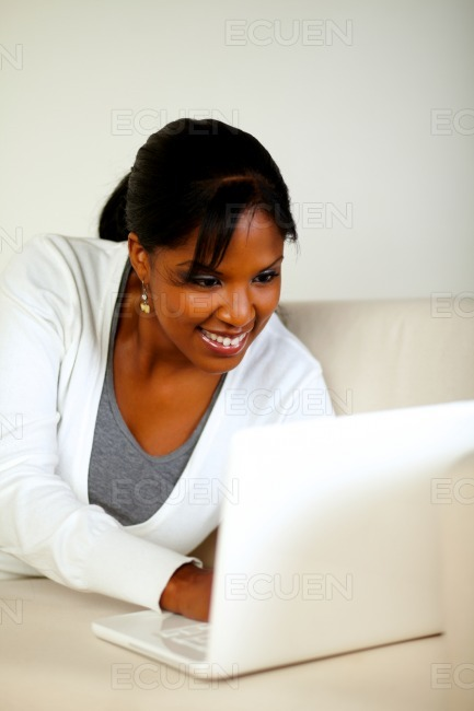 Smiling black woman looking on laptop screen stock photo