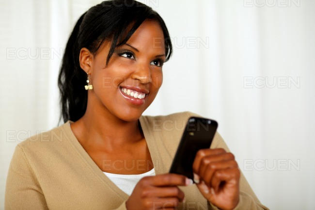 Smiling female sending a message by the cellphone stock photo