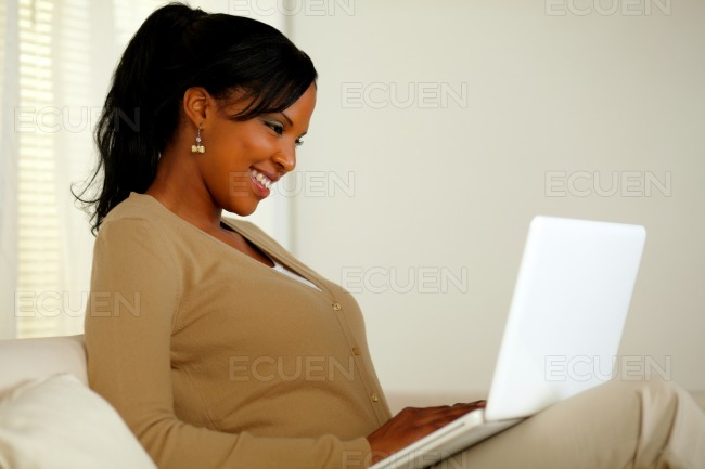 Smiling woman browsing the Internet on her laptop stock photo