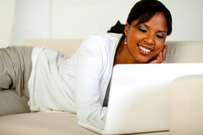 Smiling woman browsing the Internet on laptop stock photo