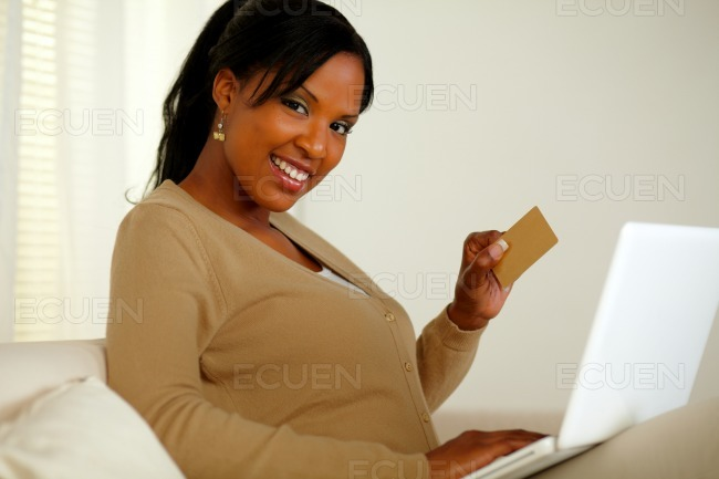 Smiling woman holding a gold credit card stock photo