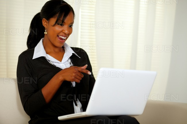 Smiling woman on black suit pointing to laptop stock photo