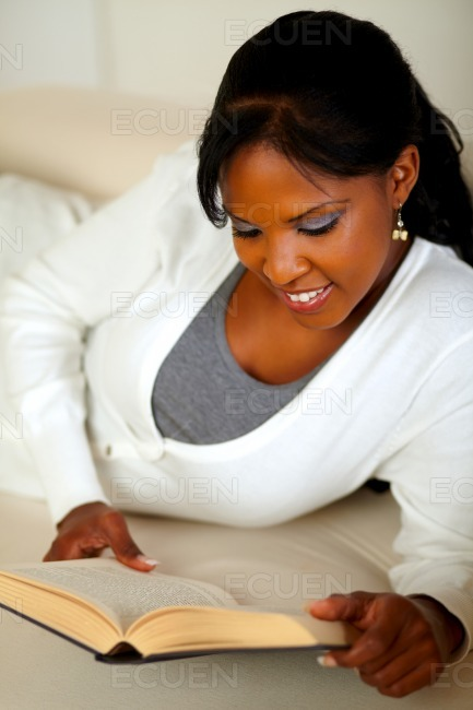 Smiling woman reading a book while lying on couch stock photo