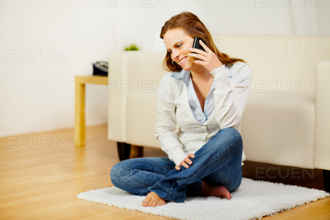 Smiling woman talking on cellphone at home stock photo