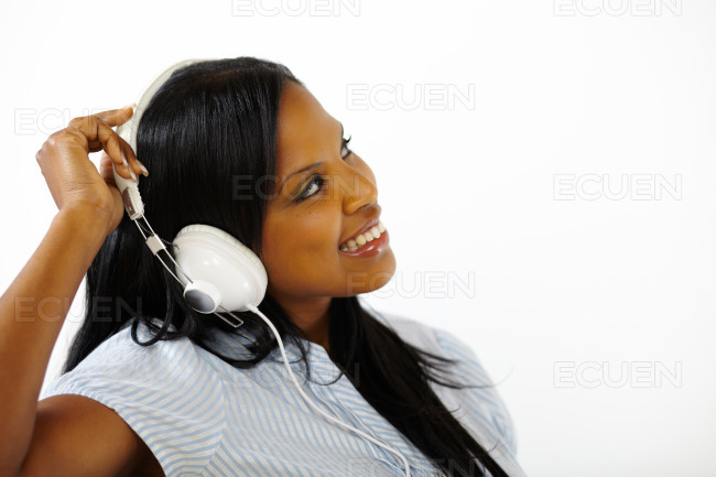 Smiling young female listening to music stock photo