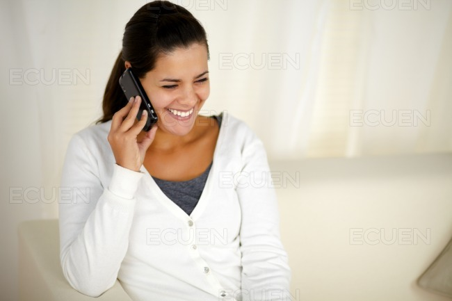 Smiling young woman conversing on cellphone stock photo