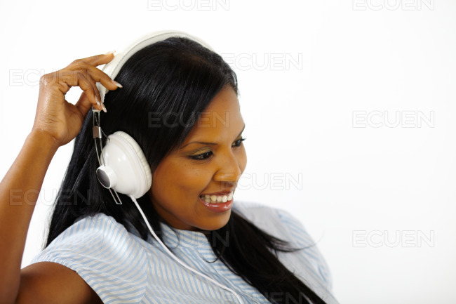 Smiling young woman listening to music stock photo