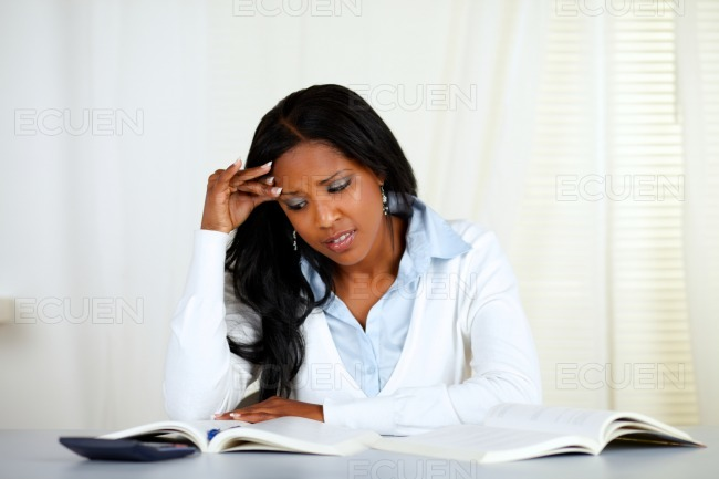 Stressed young black woman reading a book stock photo