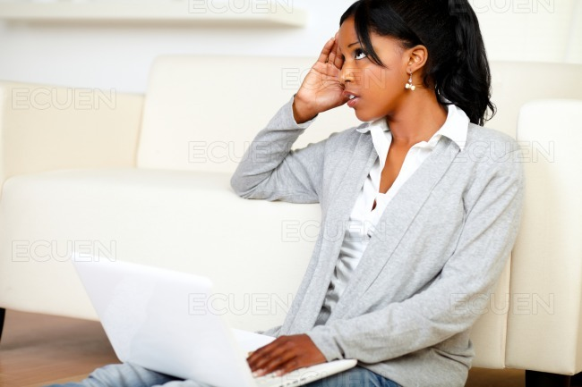 Stressed young black woman working on laptop stock photo