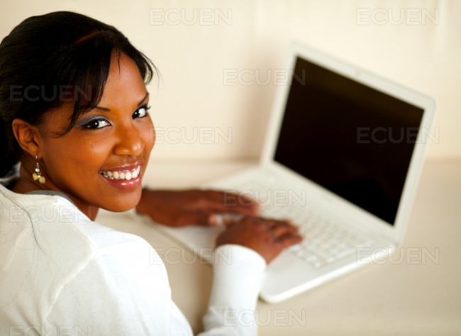 Stylish female looking at you working on laptop stock photo