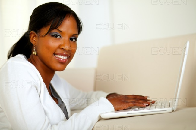 Stylish girl looking at you working on laptop stock photo