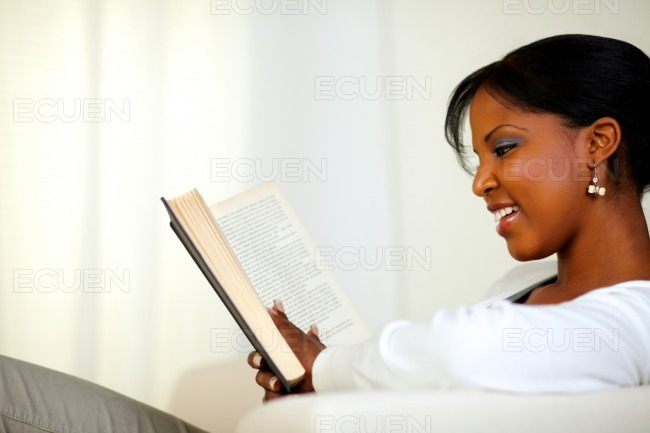 Stylish young relaxed woman reading a book stock photo