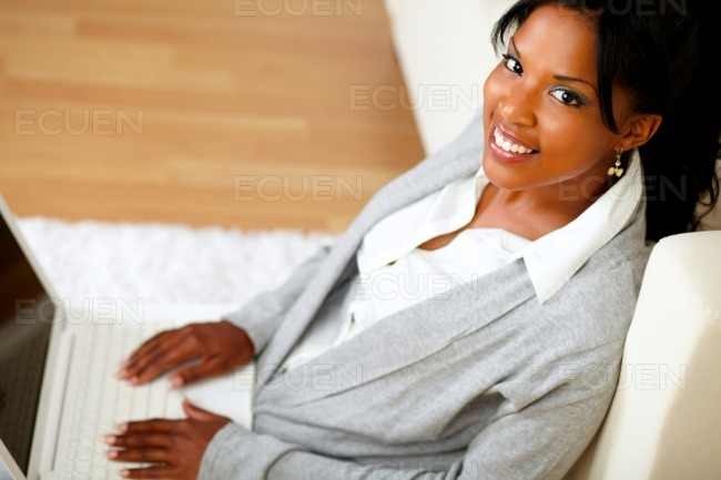 Stylish young woman with her laptop looking to you stock photo