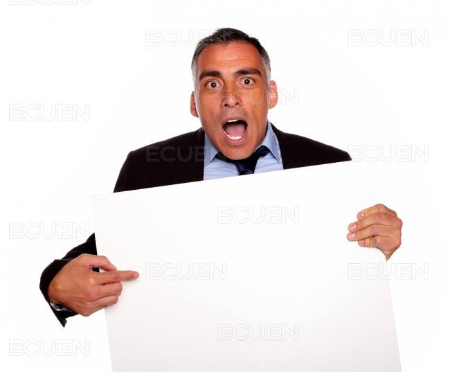 Surprised businessman pointing a card stock photo