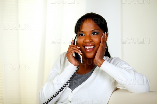 Surprised female smiling and conversing on phone stock photo