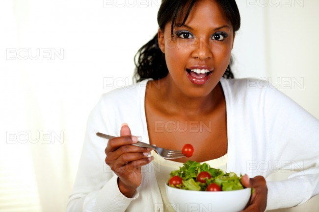 Surprised young woman eating fresh vegetable salad stock photo