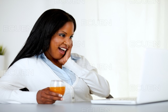 Surprised young woman looking to laptop screen stock photo