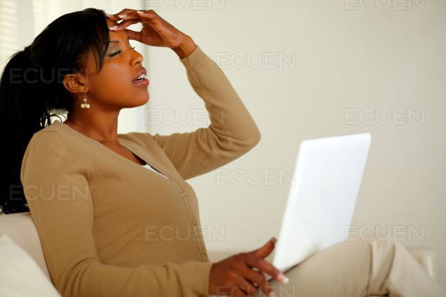 Tired woman with headache browsing the Internet stock photo