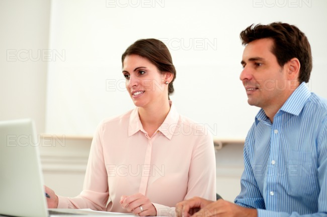 Two business colleagues looking at laptop