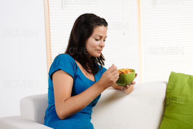 Woman eating breakfast cereal stock photo