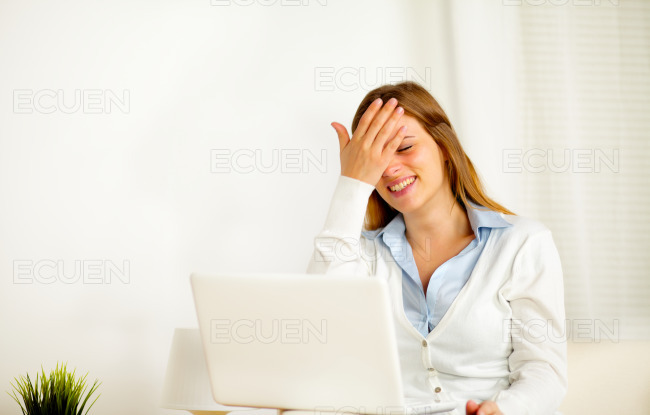 Woman laughing alone while is using on laptop stock photo