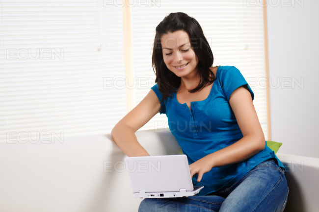 Woman laughing and using a laptop stock photo