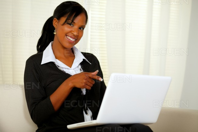 Woman on black suit pointing to laptop screen stock photo