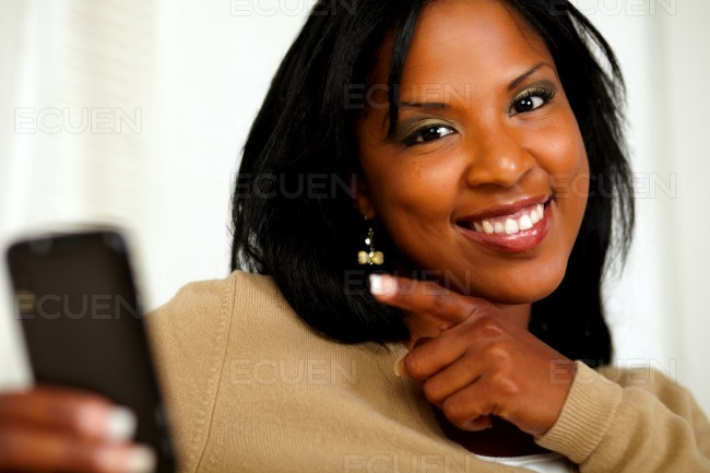 Woman pointing her cellphone and smiling at you stock photo