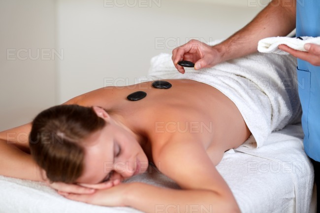 Woman relaxing while having a hot stone massage stock photo