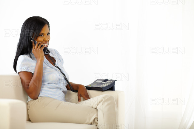 Woman talking on phone at home stock photo