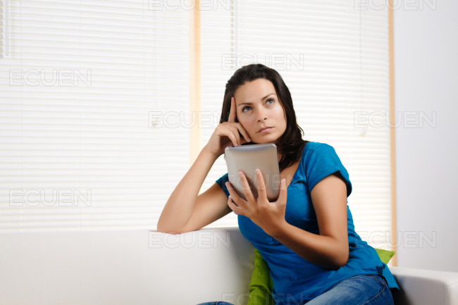 Woman thinking while holding a tablet PC stock photo