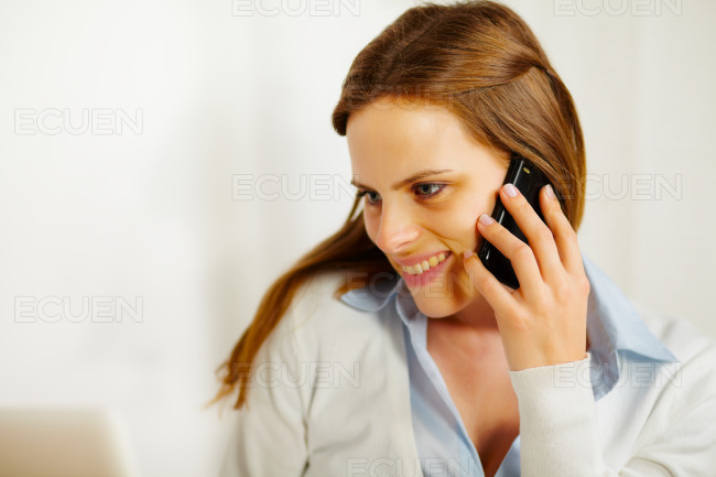 Woman working on laptop and on the phone stock photo