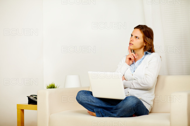 Young adult woman thinking on sofa with a laptop stock photo