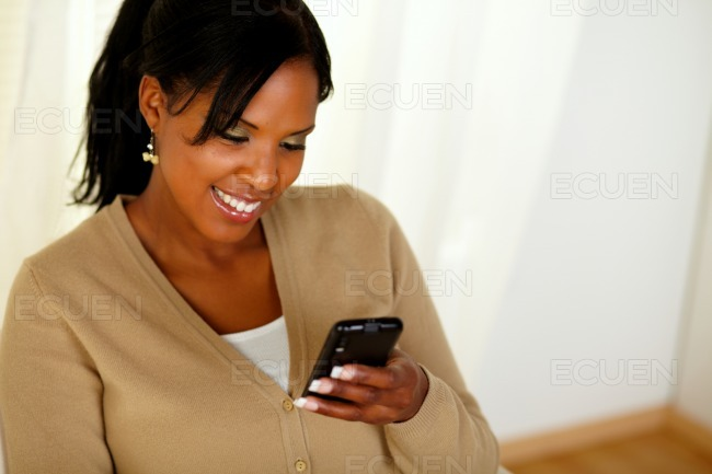 Young afro-american woman reading a message stock photo