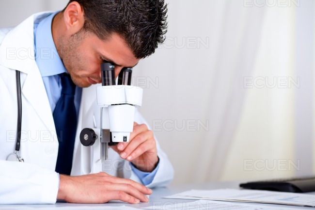 Young attractive doctor working with a microscope stock photo