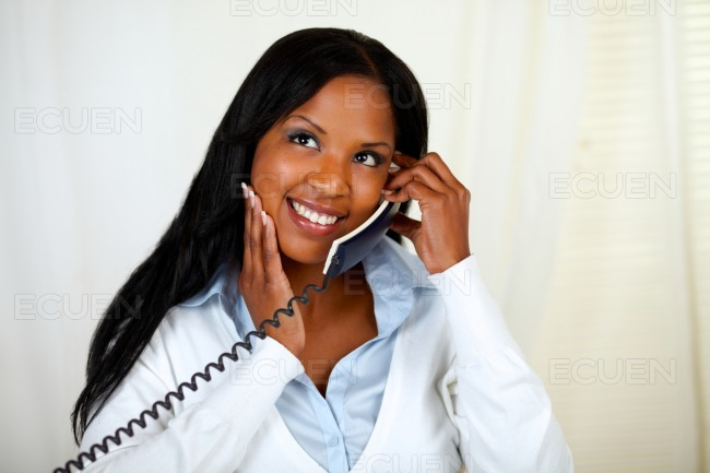 Young black lady conversing on phone stock photo