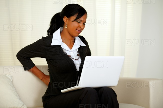Young businesswoman with back pain stock photo
