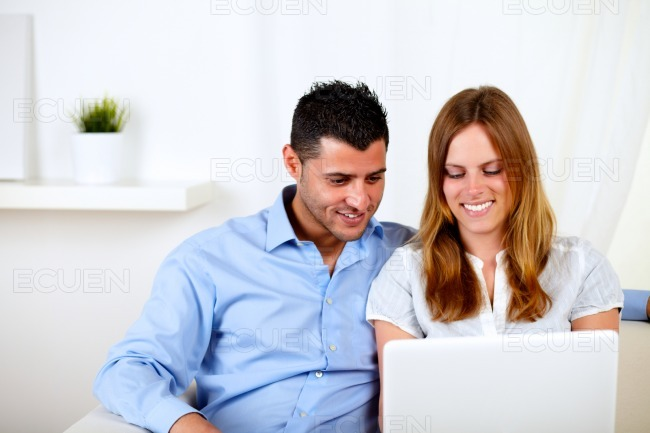 Young couple smiling and using a laptop stock photo