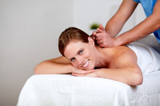 Young female getting a back massage by a masseuse stock photo