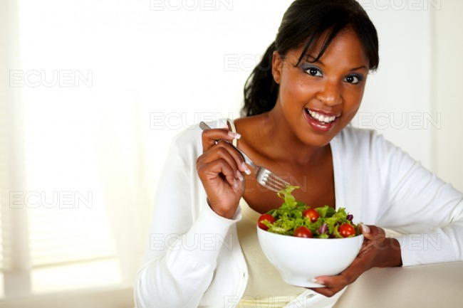 Young female looking at you while eating salad stock photo