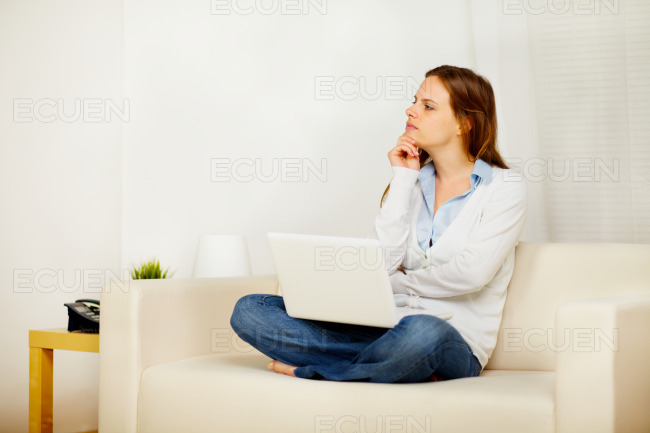 Young female thinking on sofa with a laptop stock photo