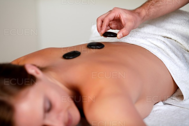Young girl relaxing and having a hot stone massage stock photo