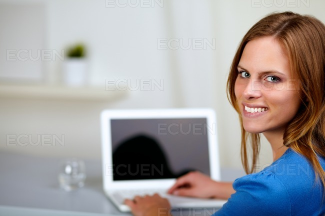Young girl smiling and working on laptop stock photo